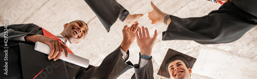 Canvas Print bottom view of happy interracial students in graduation gowns and caps holding d