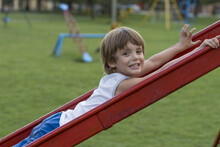 Shallow Focus Shot Of A Cheerful Caucasian Boy On A Slide In The Playground