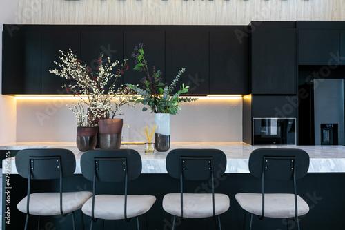 Fototapeta Bright modern kitchen with leather bar stools.