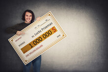 Excited Man Holding A Lottery Winner Bank Check. Happy Guy Jackpot Winning One Million Dollars Prize. Big Banner Announcing The Main Award. Wealth, Luck And Success Concept. Becoming A Millionaire