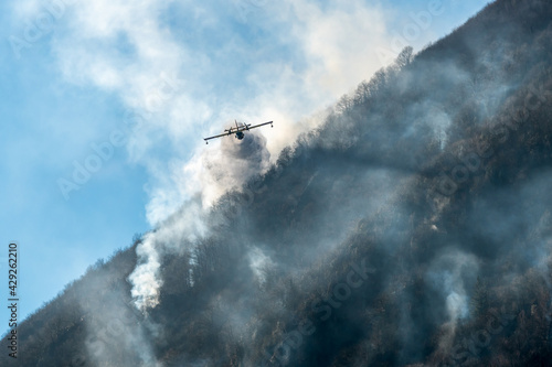 Papel de parede Firefighting Aircraft dropping the water for fighting a fire on mountain above L