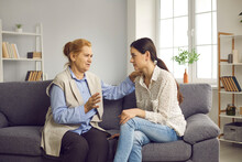 Supportive Senior Mother Talking To Her Grown-up Young Daughter While Sitting On Sofa At Home. Love, Care, Family Support, Mutual Help And Understanding Concept