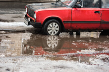 Old Red Car And Huge Puddle On Winter City Street Road
