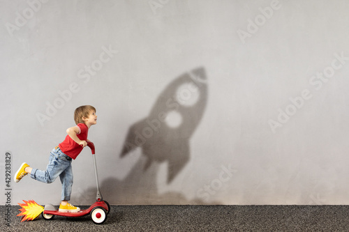 Happy kid dreams about space. Imagination, freedom and motivation concept - fototapety na wymiar