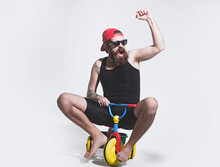Amazed Funny Bicycle Rider, Excited Man On Colorful Bicycle Toy In Sunglasses, Cap. Guy Riding Childs Tricycle.