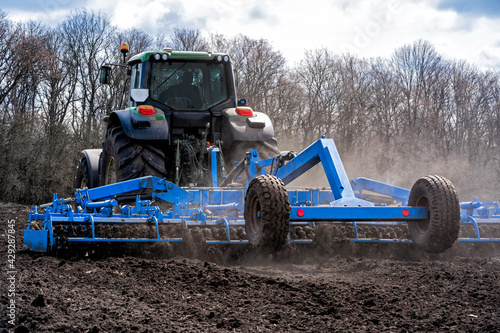 Fototapeta tillage in early spring. Tractor with aggregate