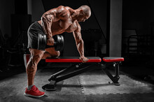 Muscular Man Pulls A Dumbbell Towards His Stomach. Bodybuilding And Powerlifting Concept.