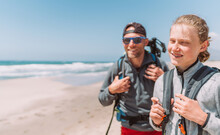 Father With Teenager Son With Backpacks Walking By The Sandy Seaside Beach. They Smiling And Looking At The Camera. Active Happy Family People Vacation Time Concept Image.