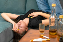Drunk Young Dark-haired Woman Lying On The Couch Upside Down After A Party Close-up With Her Eyes Closed, Empty Bottles Standing On The Table