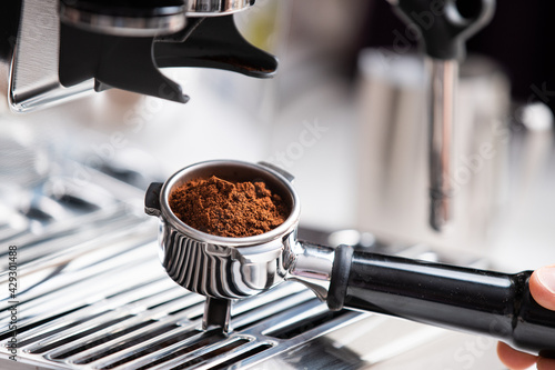 Fotografija freshly ground coffee beans in a portafilter by the coffee grinder freshly groun