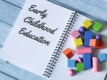Phrase Early Childhood Education Written On Notebook With A Bunch Colorful Wooden Cubes.