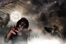 Scary Zombies At Misty Cemetery Under Full Moon. Halloween Monsters