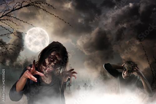 Fototapeta Scary zombies at misty cemetery under full moon