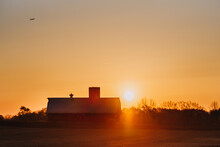 Sunrise Over A Barn And Field