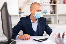 Portrait Of Young Man In Medical Mask Sitting At Desk With Laptop And Working In Office