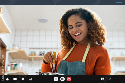 Fotografia Happy smiling young African American woman making video call while cooking in ki