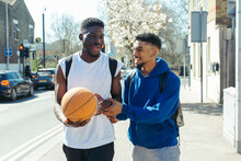 Two Friends Walking Through Street With Basketball