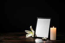 Photo Frame With Lily Flower And Candles On Table Against Dark Background