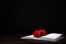 Book With Carnation Flowers On Table Against Dark Background