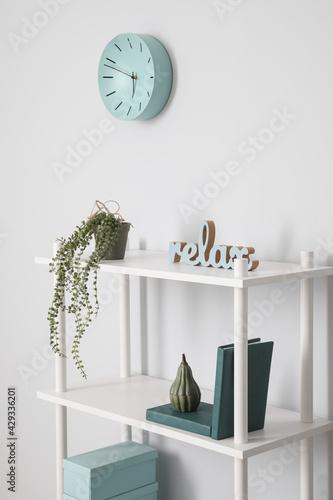 Obraz Shelf unit with clock near light wall in room - fototapety do salonu