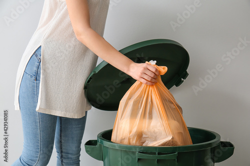 Obraz Young woman putting garbage in trash bin on light background - fototapety do salonu
