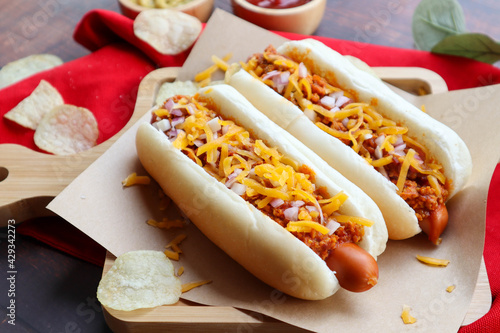 Stampa su Tela Chili dog, chili cheese hotdog served on wood tray with chips - close up view of