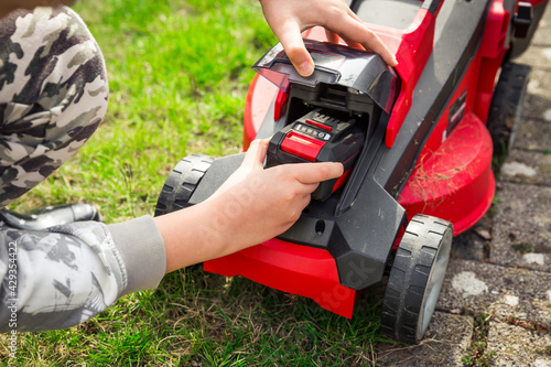 Fototapeta Teenager changes rechargeable battery in electric lawn mower obraz