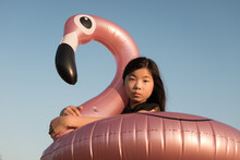 Girl Holding Pink Rubber Inflatable Flamingo Swimming Pool Ring