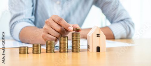 Canvas Print Asian business man putting coin increase on coins stacking with house model whil