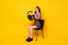Full Size Profile Photo Of Optimistic Funny Brunette Lady Sit Drive Wear Shirt Dress Sneakers Isolated On Vivid Yellow Background