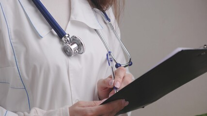 A doctor in a white coat with a stethoscope writes a prescription in a tablet with a pen, medical services from a specialist therapist, treating people at work, business concept, 4K, close-up