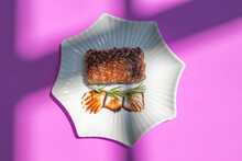 Piece Of Chocolate Brownie Cake With Icing On Plate On A Purple Abstract Background.