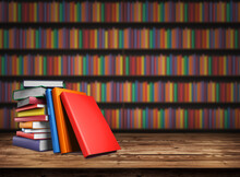 Wooden Table With A Stack Of Colored Books. Blurred Background From Book Shelves. Table Top With Books In The Library. Back To School. Background Design Element, Banner, Poster