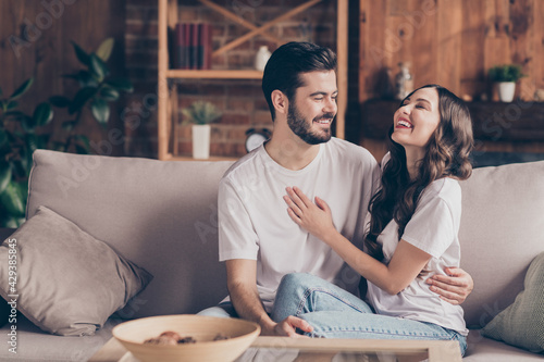 Fototapeta Photo of happy smiling cheerful positive married couple sit sofa couch enjoying