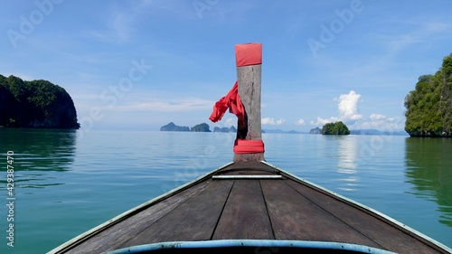 Photo Front view of prow long tail boat on the sea with mountain against blue sky