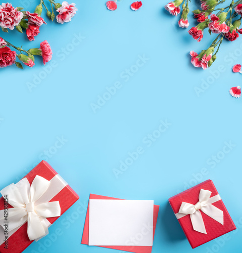 Fototapeta Mother's Day gift. Design concept of holiday greeting card with red carnation bouquet on bright blue table background obraz