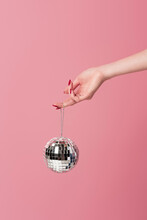 Partial View Of Woman With Red Manicure Holding Disco Ball Isolated On Pink