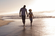 African American Father And Daughter Walking And Holding Hands At The Beach