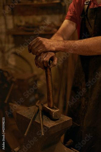 Papel de parede Blacksmith hold hammer on anvil in smithy