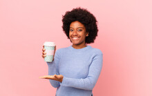 Afro Woman Smiling Cheerfully, Feeling Happy And Showing A Concept In Copy Space With Palm Of Hand. Coffee Concept