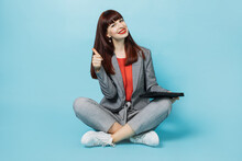Cute Charming Dark-haired Business Woman In Elegant Gray Suit, Sitting In Lotus Position With Digital Tablet In Hands, Over Blue Background In Studio, Showing Thumb Up At Camera