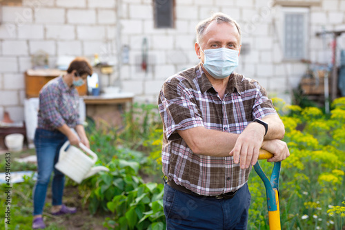 Fotografia, Obraz Man professional horticulturist in protective mask with garden shovel working at