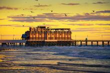 Sunrise Above Daytona Beach Main Street Pier, Florida, With A Flock Of Seagulls