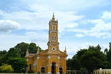 St Joseph Old Yellow Catholic Church (Beautiful Art And Architecture) In Ayutthaya, Thailand. There Are Bright Green Trees Around The Church And Blue Sky Above The Chao Phraya River In Front.