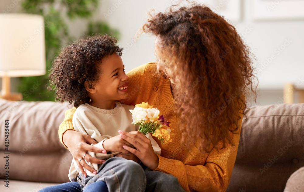 Fototapeta Cute little son giving flower bouquet his mom for Mothers day