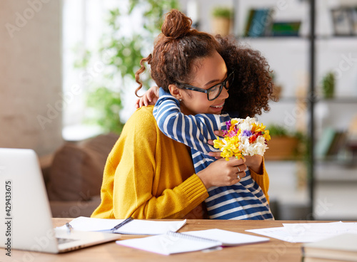 Happy mixed race woman mother with flower bouquet embracing with child while getting congratulations on Mothers day - fototapety na wymiar