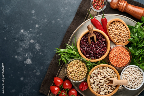 Photographie Legumes, lentils, chickpea, beans assortment, tasty appetizing ingredients spices grocery for cooking healthy kitchen on black table
