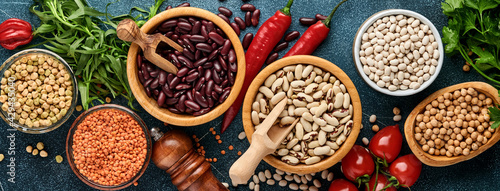 Tableau sur Toile Legumes, lentils, chickpea, beans assortment, tasty appetizing ingredients spices grocery for cooking healthy kitchen on blue table