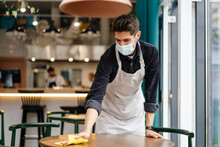Man Waiter Wearing Mask Disinfecting Table In The Cafe