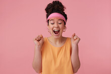 Joyful, Surprised Girl With Dark Curly Hair Bun. Wearing Pink Visor, Earrings And Orange Tank Top. Has Make Up. Clench Fists And Close Eyes In Excitement. Stand Isolated Over Pastel Pink Background